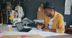 Odzieżowy projektant kreśli patrzejący laptopu ekran pracuje samotnie w studiu zdjęcie wideo