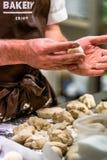 Odziena, Latvia, Sierpień/- 24th, 2018: Męski szef kuchni Przygotowywa Chlebowego ciasto dla Selfmade pasztecików i chleba fotografia stock