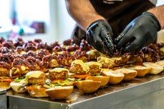 Odziena/Lettland - Augusti 24th, 2018: Manlig kock Putting Ingredients av hamburgare i svarta handskar - begrepp av det hårda arb fotografering för bildbyråer