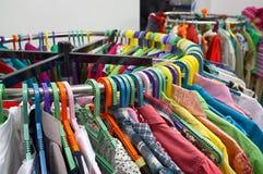 Odziewa na stojakach w sklepie. Obraz Stock
