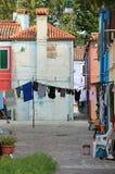 Odziewa wieszający out suszyć między dwa domami w Burano fotografia stock