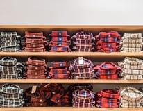 Odziewa wystawiający w sklepie Odbitkowy spase dla teksta Udział szkockiej kraty ciepłe koszula różny kolor starannie brogują z r obrazy royalty free