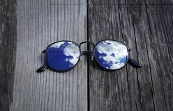 Odzwierciedlający okulary przeciwsłoneczni zamknięci up na drewnianym molu z chmurami i nieba odbiciem fotografia stock