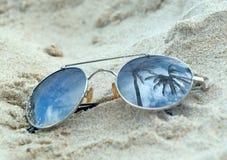 Odzwierciedlający okulary przeciwsłoneczni zamknięci up na plażowym piasku z drzewka palmowego odbiciem fotografia stock