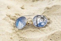 Odzwierciedlający okulary przeciwsłoneczni zamknięci up na plażowym piasku z drzewka palmowego odbiciem zdjęcie stock