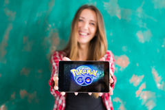 Oefa, Rusland - 29 juli: De vrouw toont de tablet met Pokemon embleem gaat Royalty-vrije Stock Fotografie