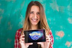 Oefa, Rusland - 29 juli: De vrouw toont de tablet met Pokemon embleem gaat Royalty-vrije Stock Afbeelding