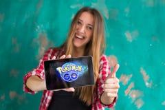 Oefa, Rusland - 29 juli: De vrouw toont de tablet met Pokemon embleem gaat Stock Afbeeldingen