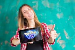 Oefa, Rusland - 29 juli: De vrouw toont de tablet met Pokemon embleem, 29 Juli, 2016 in Oefa, Rusland gaat Stock Afbeelding