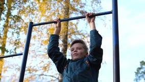 Oefening in de verse lucht Jonge sterke kerel die oefeningen op de bar doen De herfstpark stock video