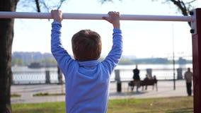 Oefening in de verse lucht Weinig jongen die oefeningen op de bar doen Het park van de zomer stock video