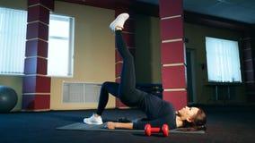 Oefening die het bekken met één voet opheffen Het meisje voert een oefening op de spieren van de billen uit stock videobeelden
