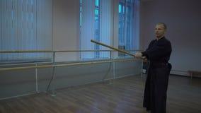 Oefening met het kendo hoofd` s houten zwaard in de blauwe kimono vroeg in de ochtend in de sporthal stock videobeelden