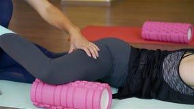 Oefening op een schuimrol bij pilatesstudio stock footage