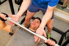 Oefeningen voor de borsten met barbell in de gymnastiek Royalty-vrije Stock Foto's
