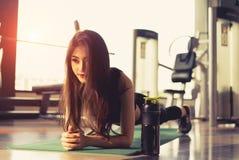 Oefeningsvrouw die plank doen bij de geschiktheid van de gymnastiektraining stock foto