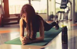 Oefeningsvrouw die plank doen bij gymnastiektraining stock fotografie
