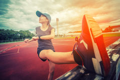 Oefeningsvrouw het uitrekken zich verlamt beenspieren tijdens openlucht lopende training Het glimlachen van gelukkige gemengde ra stock foto