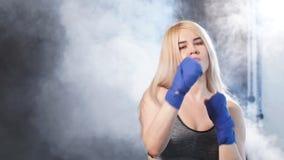 Oefent de blonde vrouwelijke atleet in defensie op donkere rokerige achtergrond uit Langzame Motie stock videobeelden