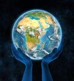 Oeganda op aarde in handen Stock Afbeelding