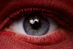 Oeil de beauté avec la peinture rouge foncé sur la peau Photographie stock libre de droits