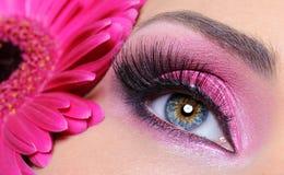 Oeil de femme avec le renivellement rose et la fleur Photographie stock libre de droits
