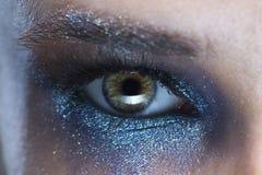 Oeil de la jeune femme avec une photo bleue de macro de maquillage d'avant-garde images stock