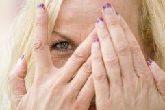 Oeil derrière des doigts photographie stock libre de droits