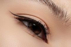 Oeil femelle de beau plan rapproché avec le maquillage de revêtement de noir de mode Images libres de droits