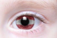 Oeil humain avec le drapeau national de la Lettonie Image stock
