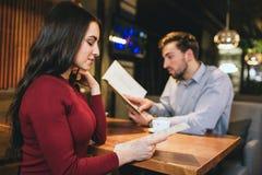 Oeil plus attentif à une fille renversante s'asseyant avec son ami dans un restaurant Chacun d'eux regardent au menu Ils veulent Photos stock