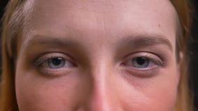 Oeil-portrait en gros plan de la femme formel-habillée observant calmement dans la caméra sur le fond noir banque de vidéos