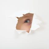 Oeil regardant par le trou en feuille de papier Photographie stock libre de droits