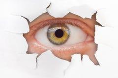 Oeil regardant par le trou sur le papier photos stock