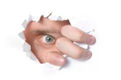Oeil regardant par un trou en papier Photographie stock