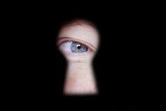Oeil vous regardant par le trou de la serrure de porte Photographie stock