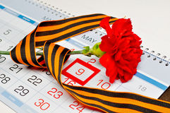 Oeillet rouge lumineux enveloppé avec le ruban de George se trouvant sur le calendrier avec la date encadrée du 9 mai Photographie stock libre de droits