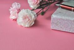 Oeillets roses et carnet floral avec un stylo sur un fond rose lumineux, image féminine dénommée avec l'espace de copie Photographie stock