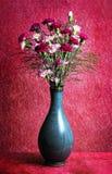 Oeillets roses et rouges dans le vase bleu sur le fond rose, le fond de fleur pour le ressort ou la Pâques Images stock