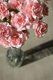 Oeillets roses sur le vieux bois et vase Photo stock