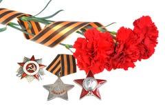 Oeillets rouges attachés avec le ruban de St George, ordres de grande guerre patriotique Photos stock