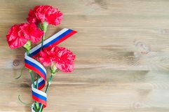 Oeillets rouges et ruban russe de drapeau se trouvant sur le fond en bois Photo libre de droits