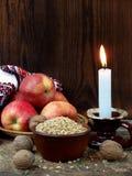 Oekraïens Kerstmisconcept voor groetkaart Samenstelling van het branden van kaars, appelen, okkernoten, tarwe op houten achtergro Stock Afbeelding