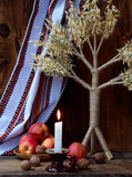 Oekraïens Kerstmisconcept voor groetkaart Samenstelling van Kerstmissymbool didukh, brandende kaars, appelen, okkernoten op houte Stock Fotografie