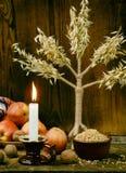 Oekraïens Kerstmisconcept voor groetkaart Samenstelling van Kerstmissymbool didukh, brandende kaars, appelen, okkernoten, tarwe o Stock Fotografie