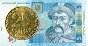 25 Oekraïens kopiykamuntstuk tegen 5 Oekraïens hryvniabankbiljet royalty-vrije stock foto