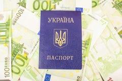 Oekraïens paspoort tegen de achtergrond van euro-Rekeningen met een nominale waarde van 100 Royalty-vrije Stock Afbeeldingen