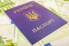 Oekraïens paspoort tegen de achtergrond van euro-Rekeningen met een nominale waarde van 100 Stock Afbeelding