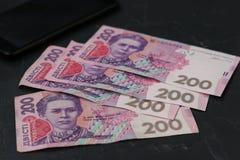 Oekraïense bankbiljetten twee honderd hryvnia en smartphone, geldachtergrond royalty-vrije stock afbeeldingen