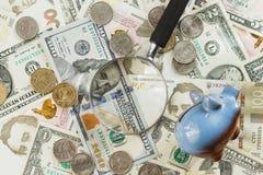 Oekraïense hryvnia en de Amerikaanse dollars van ` s met een spaarvarken en een vergrootglas Stock Foto's